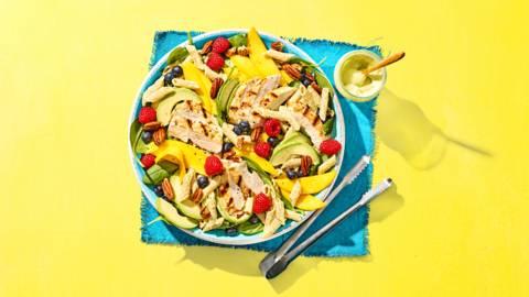 Pastasalade kip kerrie met avocadodressing, pecannoten, babyspinazie en zomerfruit