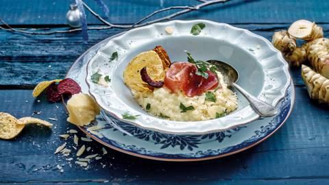 Aardperenrisotto geserveerd met prosciutto, Parmigiano Reggiano en groentechips
