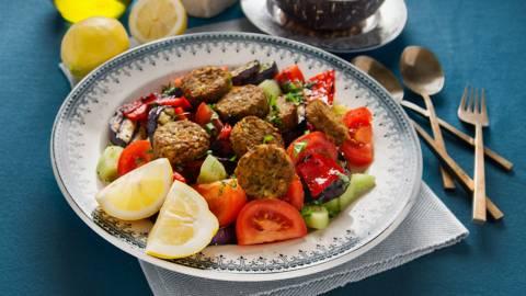 Falafel op komkommer-tomaatsalade met gegrilde aubergine en paprika's met yoghurt-knoflooksaus