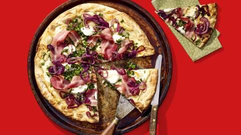 Bloemkoolpizza met boerenkool, knapperig ontbijtspek, gekaramelliseerde rode ui, geitenkaas en honing