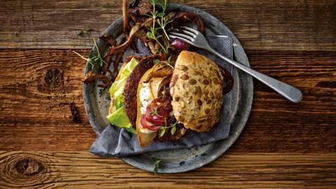 Vegetarische herfstburger met oesterzwammen, gekaramelliseerde rode uien en gegratineerde plakjes peer met geitenkaas