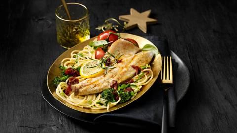 Gemarineerde zeebaarsfilet met chiliboter geserveerd op een pasta met bimi, zongedroogde tomaatjes en kruiden