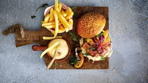 Broodje hamburger met spek, zuurkool, appel, mosterdmayonaise en verse friet