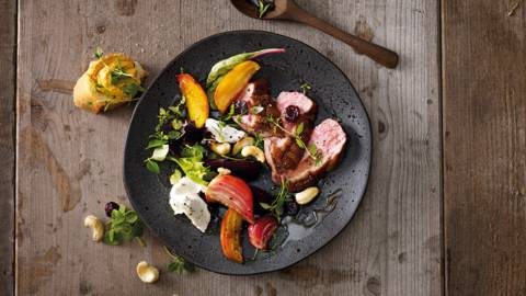 Geroosterde bietensalade met plakjes eendenborstfilet, geitenkaas en cashew-cranberrymix