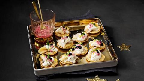 Blini's met gerookte heilbot, Griekse yoghurt, zwarte kaviaar en gemarineerde ui met bieslook