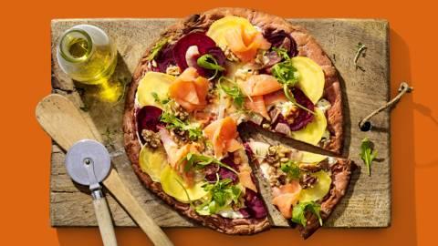 Rode bietenpizza met peer, walnootkaas, gerookte zalm, gekleurde bietjes en rucola