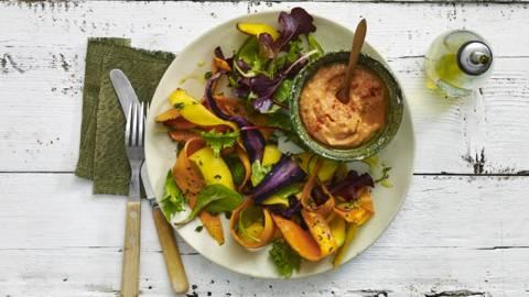 Dunne linten geroosterde gekleurde wortels met bonenhumus en rucolaslamelange