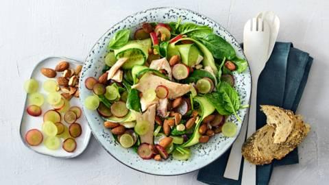 Salade met druiven, forel, komkommer, babyspinazie en geroosterde amandelen
