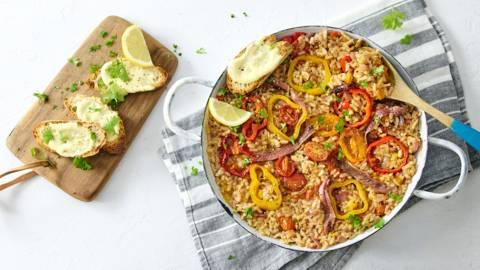 Paella met ansjovis, paprika, tomaatjes en stokbrood