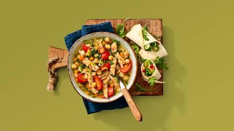 Rijkgevulde groentesoep met vegetarische kipstukjes en snacktomaatjes, geserveerd met een gevulde wrap