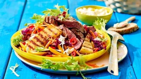 Ribeye salade met mango, bospeen en gegrilde ananas, geserveerd met stokbrood en roomkaas perzik-ananas