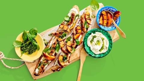 Reuze crostini's van de BBQ met gegrilde nectarines, chipolataworstjes, geitenkaasspread, basilicum en pesto