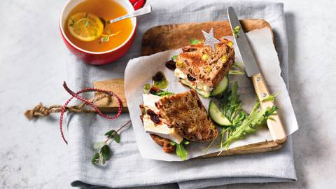 Sandwich van noten- en vruchtenbrood met cranberry-brie, komkommer en pesto