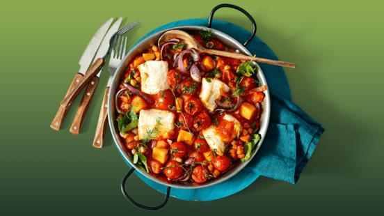 Pompoen stoofpot met kabeljauw, spinazie en kikkererwten geserveerd met geroosterde cherry trostomaten