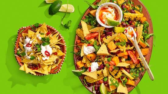 Mexicaanse salade met zoete aardappel, mais en bonen geserveerd met tacochips en chili-dip