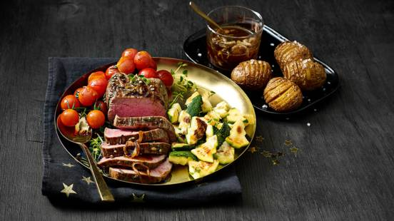 Rosbief gemarineerd met peperkorrels geserveerd met sherryjus, hasselback potatoes, courgette en cherrytomaatjes