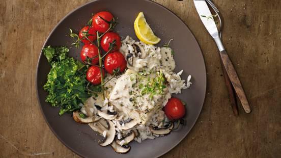 Kabeljauwhaasjes met paddenstoelensaus geserveerd met kruidenrijst, geroerbakte boerenkool en tomaatjes uit de oven