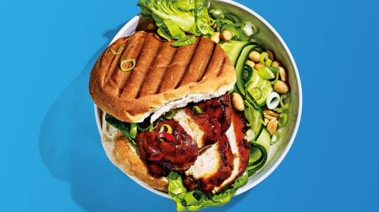 Sticky chickenburger geserveerd met mini romanasla, komkommer, lente-ui en pinda's