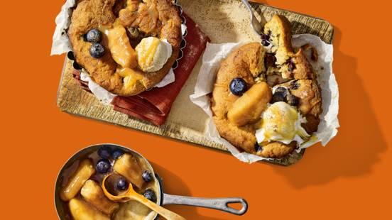 Warme herfsttaartjes met stoofappelpartjes en blauwe bessen geserveerd met vanille-ijs en karamel-zeezoutsaus