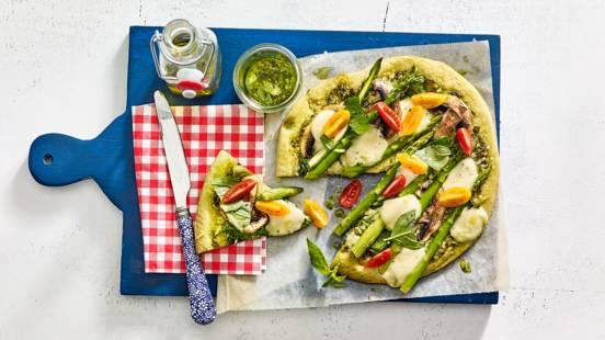 Vegetarische pizza van groente-pizzabodem met groene asperges, spinazie en champignons