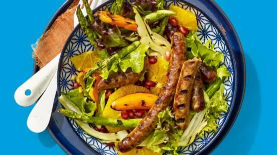 Gegrilde bio runderchipolata's met een salade van gegrilde venkel, granaatappel, lente-ui, groene asperges en sinaasappel