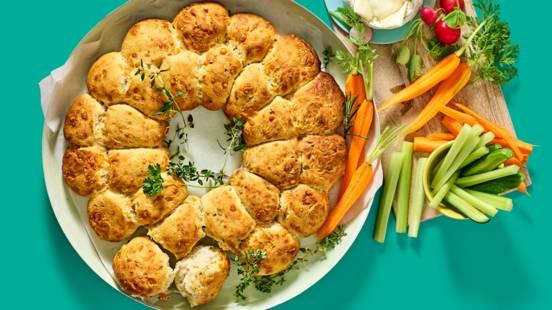 Lentekrans van zelfgebakken kaasbroodjes met warme geitenkaascamembert en crudité