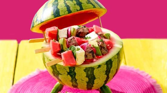Zomerse prikkers met biefstuk, watermeloen, avocado en feta geserveerd op een watermeloen-BBQ
