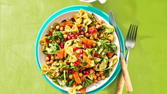 Vegetarische pastasalade met hummus, granaatappel, kikkererwten en verse pesto
