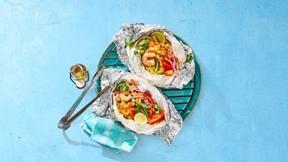 Garnalen tomatencurry pakketjes met gele rijst, groene asperges en kokos
