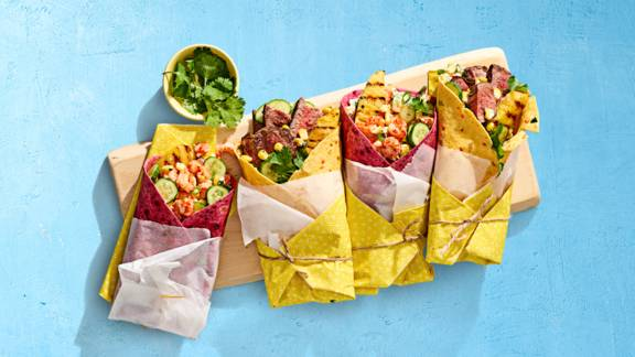 Frisse lente groentewraps met biefstuk of rivierkreeftjes, snackkomkommer, lente ui, koriander, limoen, mais, crème fraîche en gegrilde ananas