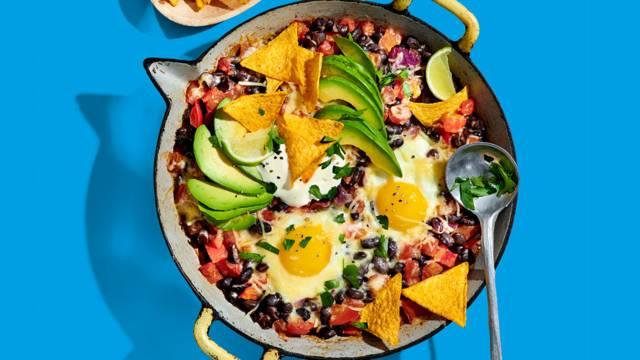 Huevos rancheros -  gestoofde zwarte bonen tomatensaus met ei, avocado, limoen en kaas
