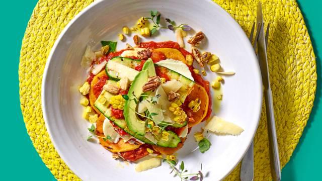 Open lasagne van courgette en zoete aardappel met mais, avocado en pecannotenmix