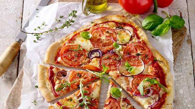 Huisgemaakte pizza met trostomaten, mozzarella en basilicum
