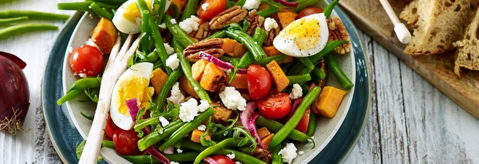 Sperziebonensalade met zoete aardappelblokjes, cherrytomaten, pecannoten en gemarineerde rode uien