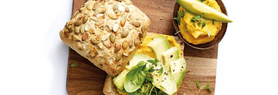 Pompoenhoumous op een broodje met avocado en verse kruiden