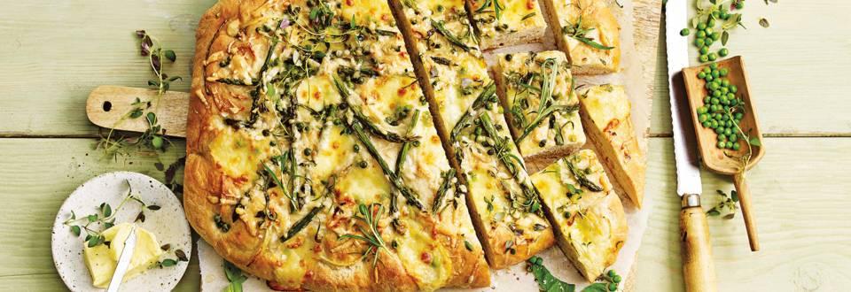 Versgebakken lente-focaccia met mozzarella, aspergetips, doperwten en citroen