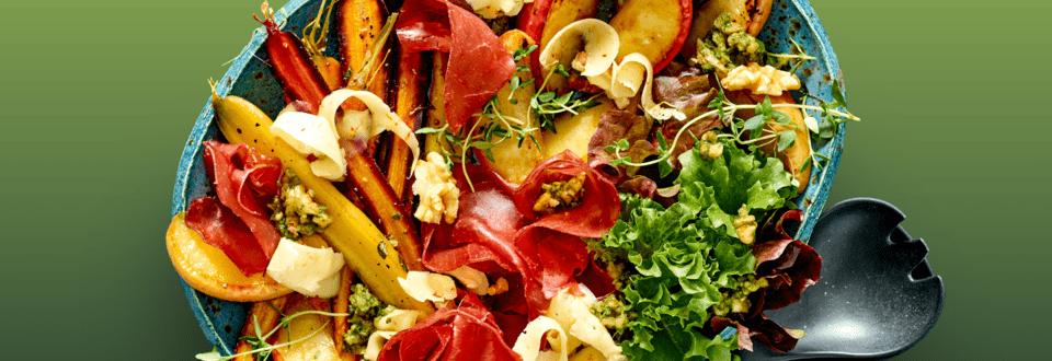 Salade met Bresaola, geroosterde regenboogwortels, herfstkaas van de boerderij, walnoten pesto en gekarameliseerde appeltjes