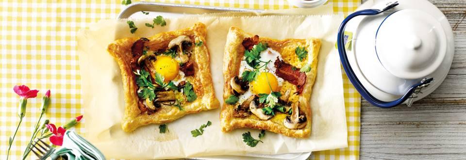 Bladerdeegtaartjes met een spiegeleitje, champignons en ontbijtspek