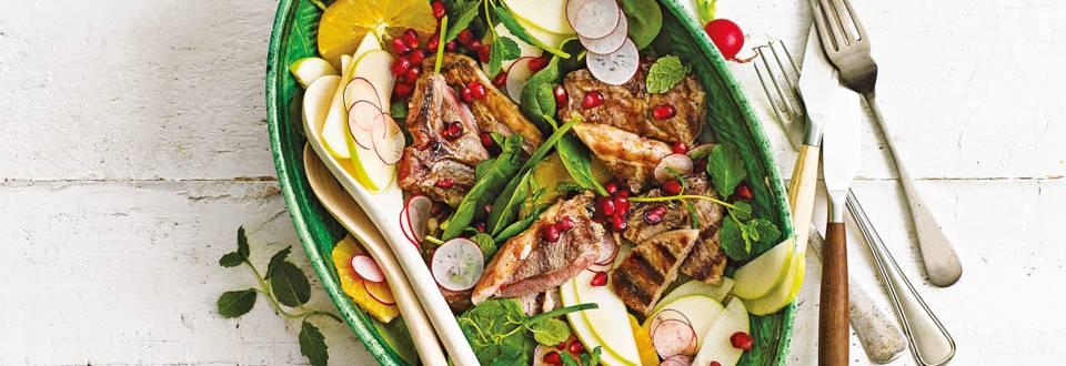 Kleurrijke salade met sinaasappel, appel, granaatappel en gegrilde lamskotelet