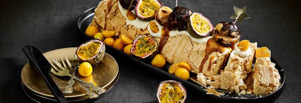 Meringue rol gevuld met room en passievrucht, versierd met salted karamel profiteroles