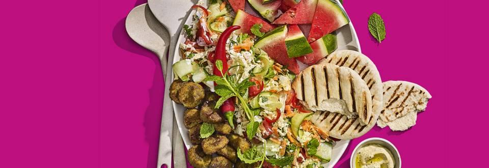 Komkommer-watermeloensalade met falafelballetjes, gegrilde pitabroodjes en houmous