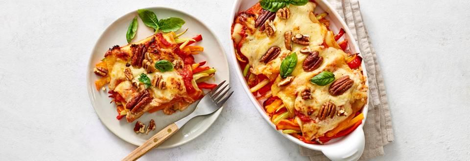 Lasagnerolletjes met gekleurde groenten, kaassaus en nootjes