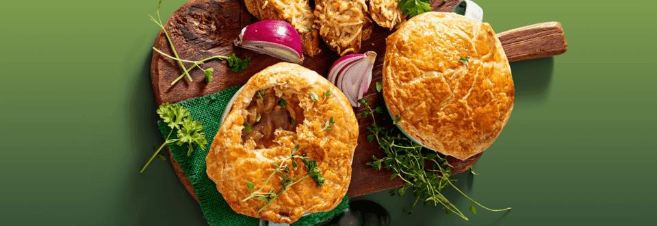 Uiensoep met een dakje van knapperig bladerdeeg geserveerd met broodjes gegratineerde kaas en verse kruiden