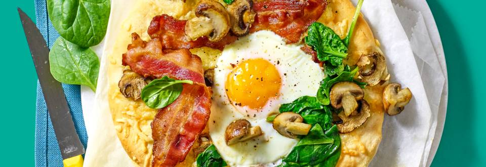 Breakfastpizza met champignons, ei, kaas, spinazie en bacon