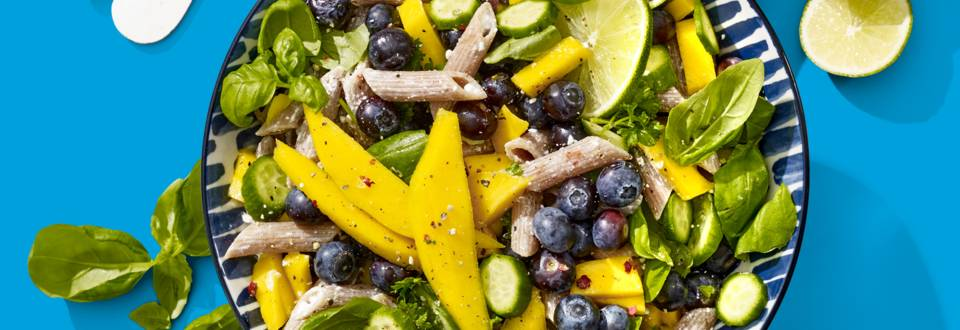 Frisse volkorenpastasalade met mango, blauwe bessen, limoen, groene kruiden en snackkomkommer