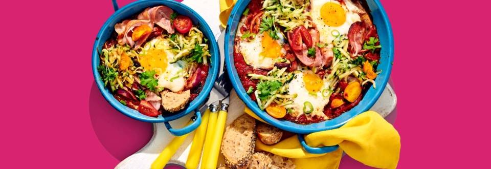 Shakshuka met geraspte courgette, ontbijtspek en lente-ui
