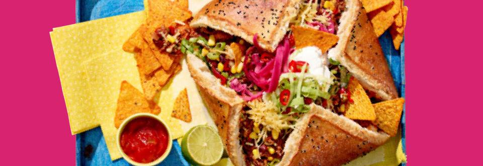 Gevuld pidebrood met Mexicaanse gehaktsaus, gemarineerde rode ui, gesmolten kaas en tacochips