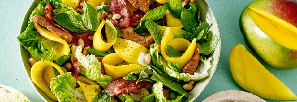 Salade van mini romanasla, gebakken ontbijtspek, mango en ketjapkip