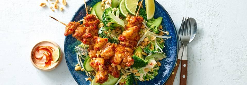 Kipdij saté geserveerd met Aziatische spicy broccolisalade en pinda's
